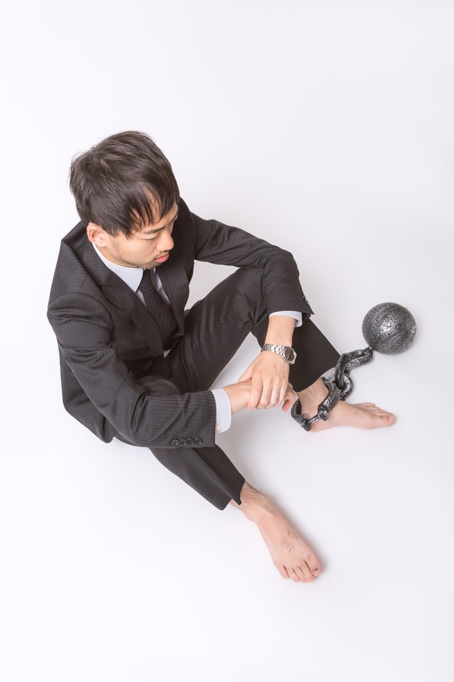 足枷と鉄球で逃げることを許されない会社員の写真