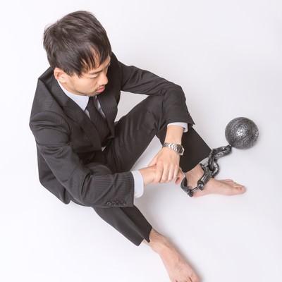 「足枷と鉄球で逃げることを許されない会社員」の写真素材
