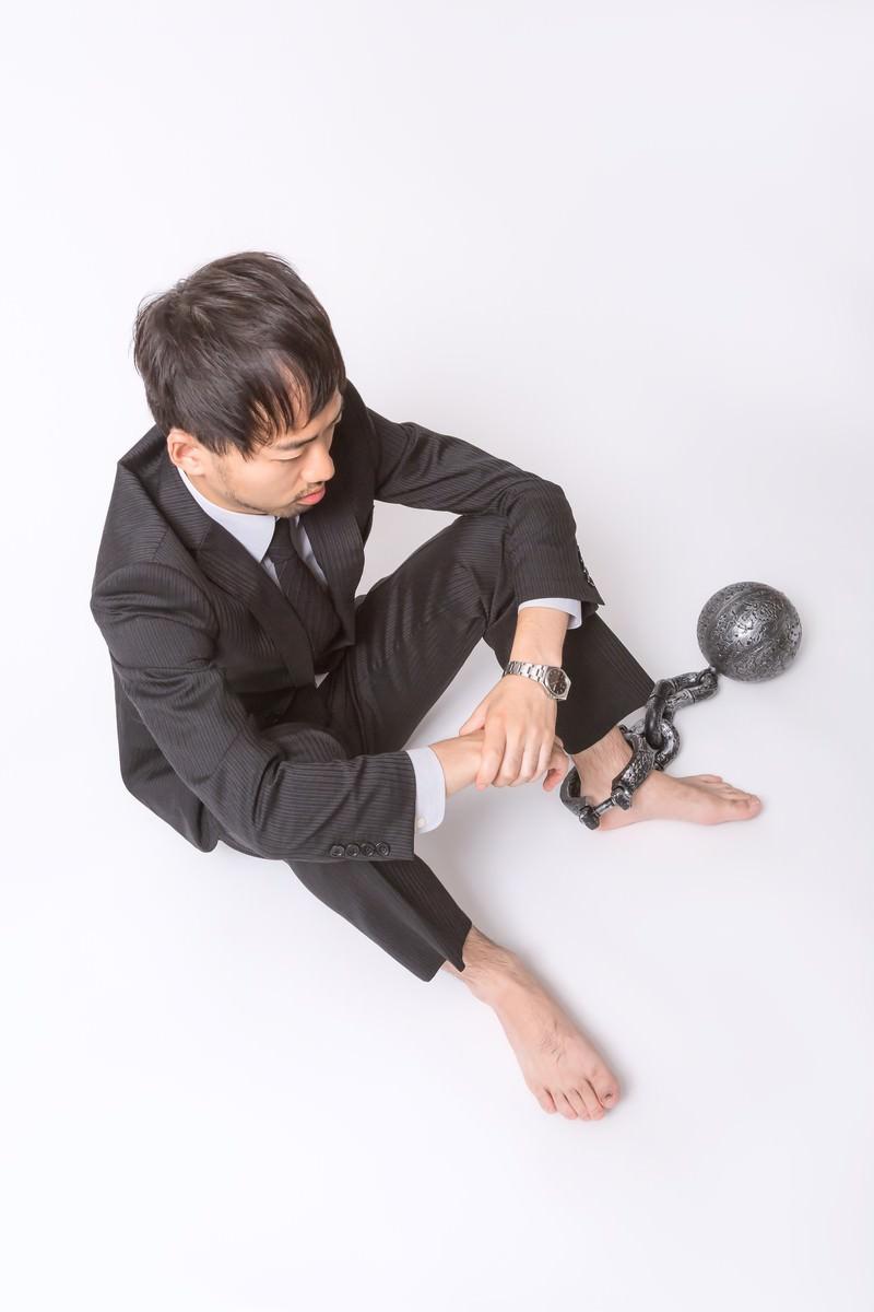 「足枷と鉄球で逃げることを許されない会社員」の写真[モデル:ひろゆき]