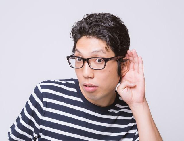 耳に手をあてる男性の写真