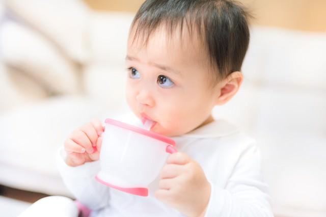 ジュースを飲むと上機嫌の赤ちゃんの写真