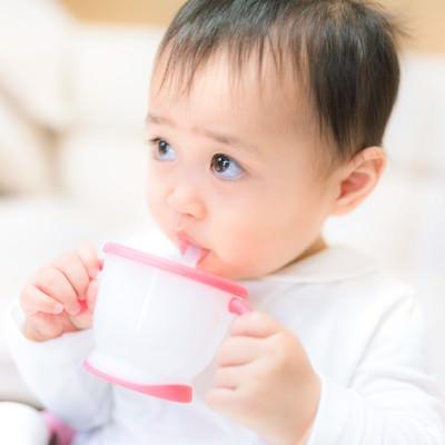 「ジュースを飲むと上機嫌の赤ちゃん」の写真素材