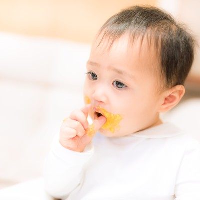 「離乳食が口の周りにべっとり付いた赤ちゃん」の写真素材