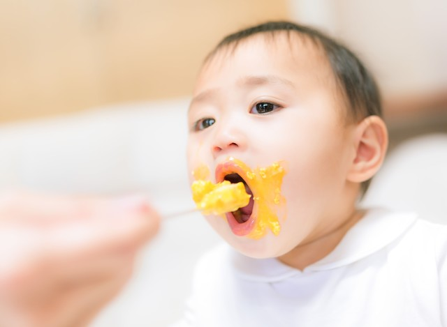 離乳食で口元ぐちゃぐちゃな赤ちゃんの写真