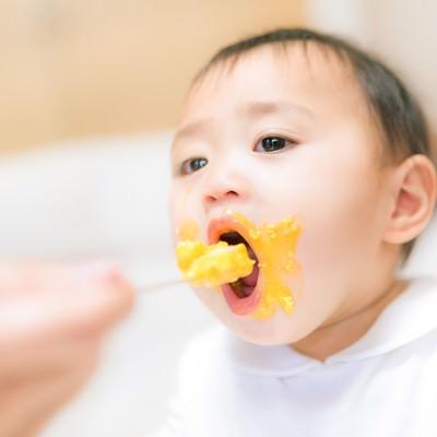 「離乳食で口元ぐちゃぐちゃな赤ちゃん」の写真素材