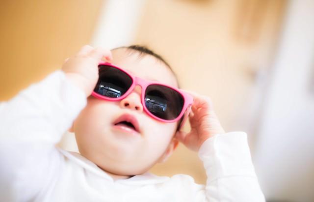 大きなサングラスをかける赤ちゃんの写真