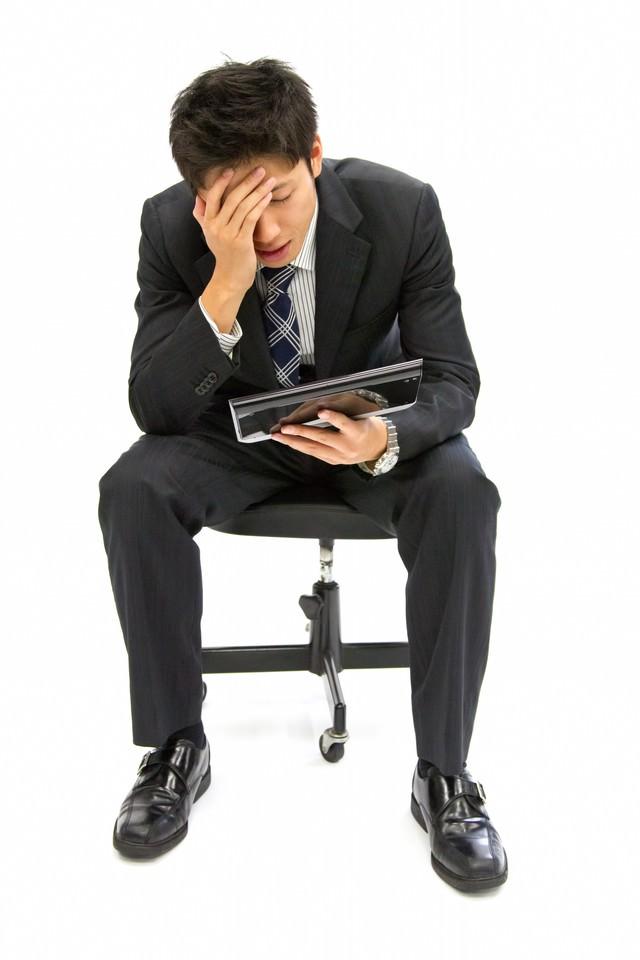 タブレットを持ち考え込むビジネスマン