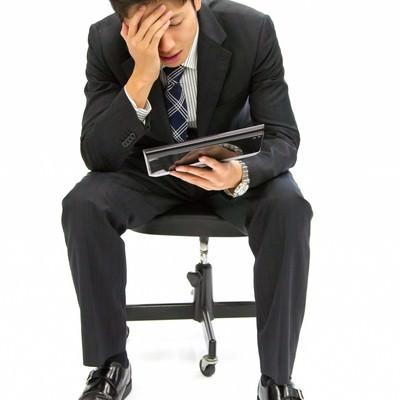 「タブレットを持ち考え込むビジネスマン」の写真素材