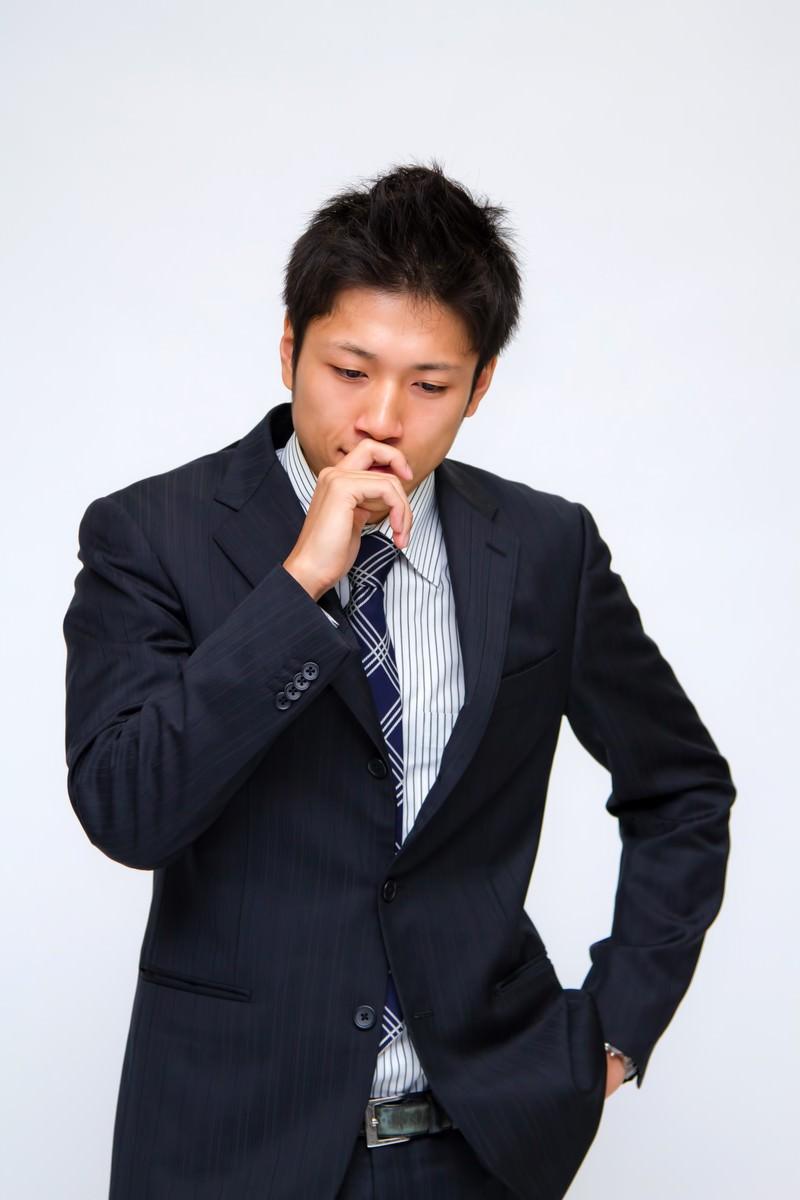 「ポケットに手を入れて考え込む男性」の写真[モデル:恭平]
