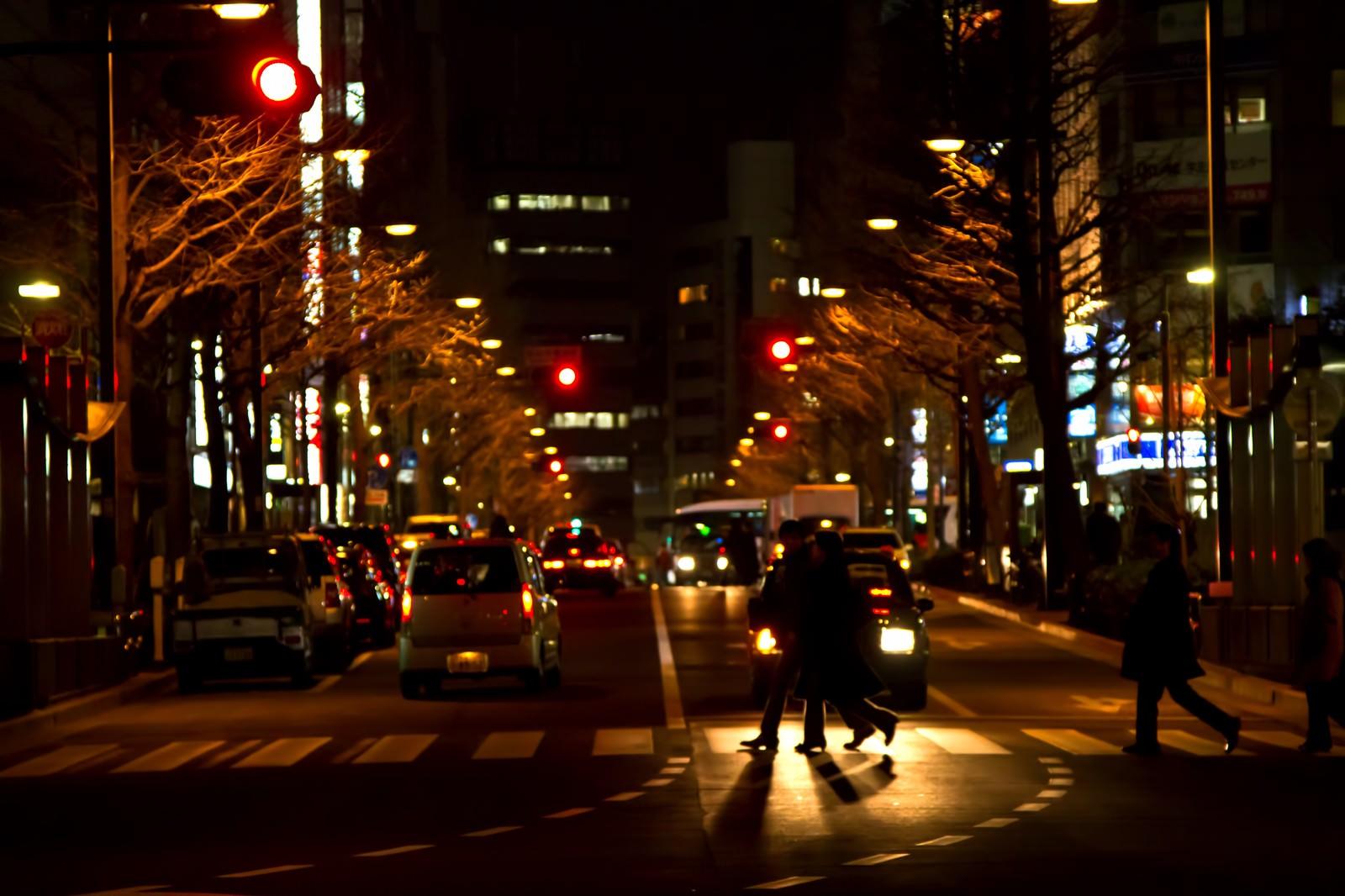 「夜、大通りの横断歩道を渡る人」の写真