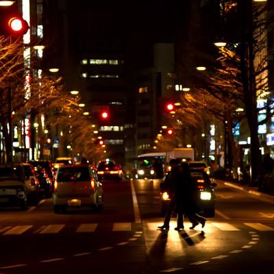「夜、大通りの横断歩道を渡る人」の写真素材