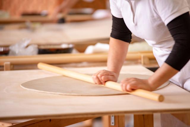 生地を伸ばす蕎麦打ち職人(武石観光センター)の写真