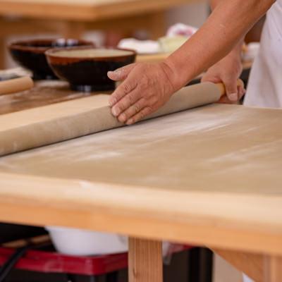 生地を丁寧に巻き上げる蕎麦打ち職人(武石観光センター)の写真