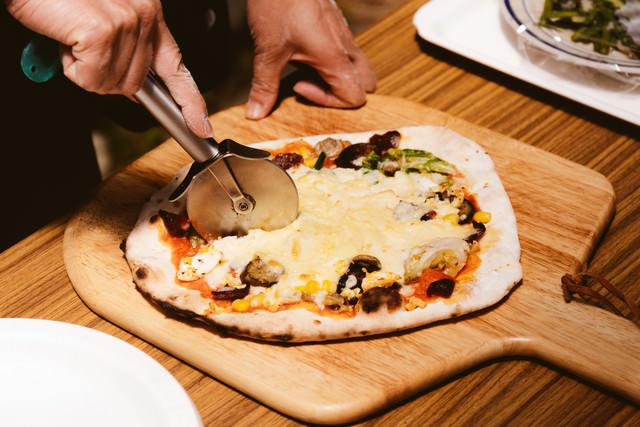 カッティングボードに乗せられたピザの写真