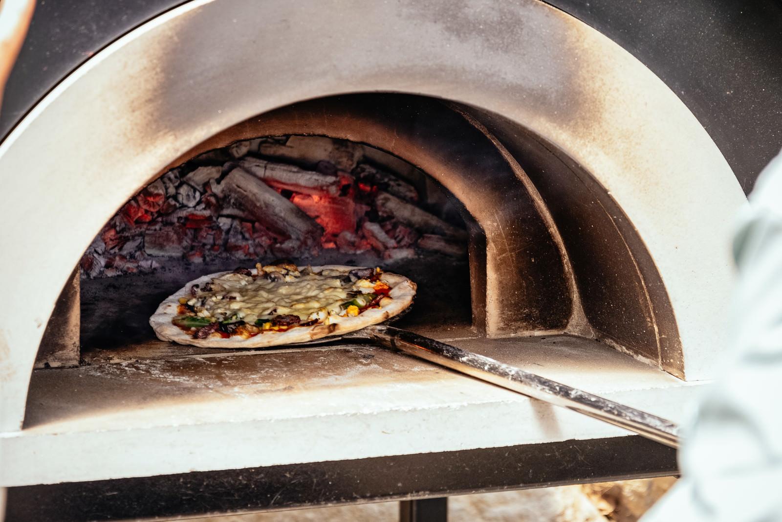 「釜から取り出されるピザ」の写真