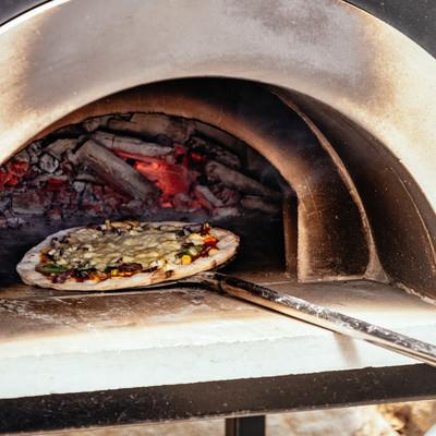 釜から取り出されるピザの写真