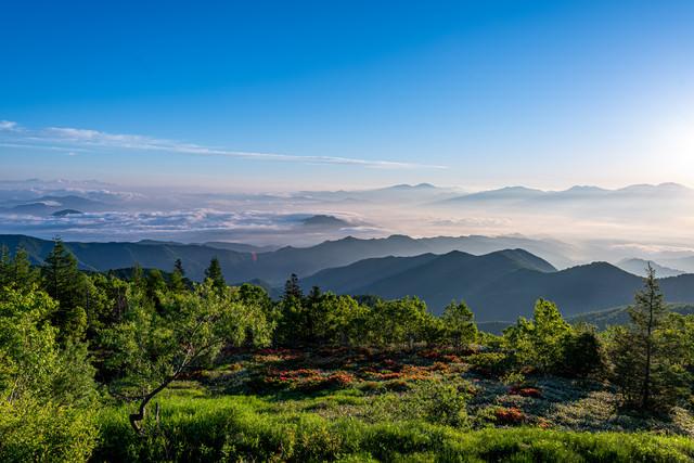 山頂から見る雲海と山並みの写真