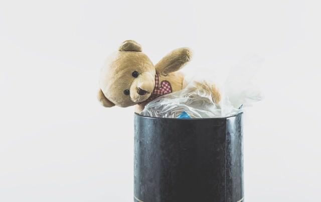ゴミ箱に捨てられたクマのぬいぐるみの写真