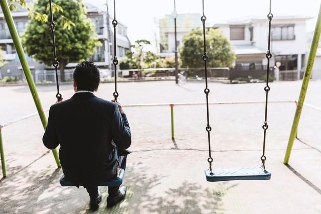 公園のブランコで時間を潰す後ろ姿が切ないビジネスマン(ドイツ人ハーフ)の写真