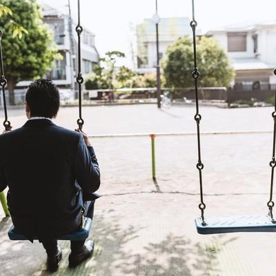 「公園のブランコで時間を潰す後ろ姿が切ないビジネスマン(ドイツ人ハーフ)」の写真素材