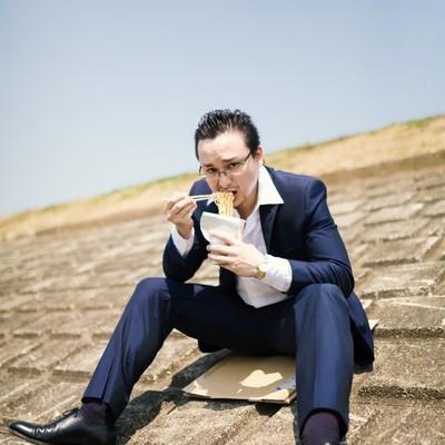 土手で昼食を済ます営業中のビジネスマンの写真