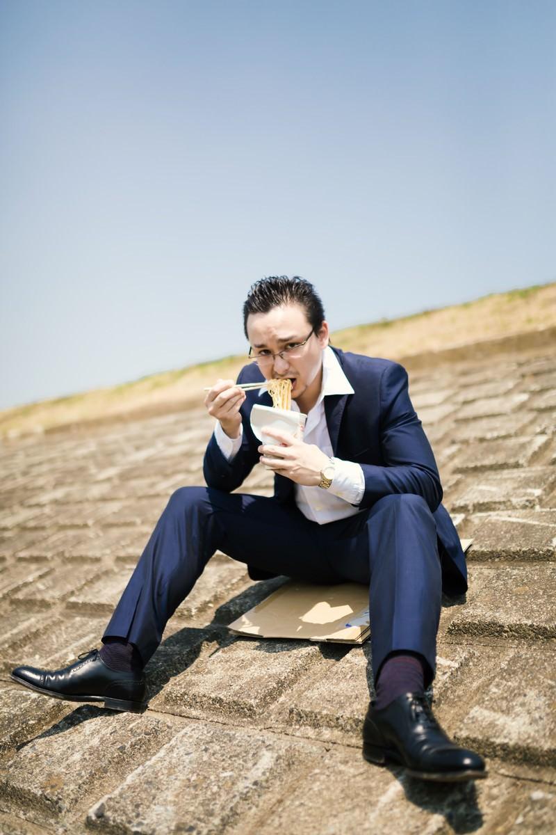 「土手で昼食を済ます営業中のビジネスマン」の写真[モデル:Max_Ezaki]