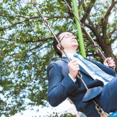 ブランコで黄昏れるビジネスマンの写真