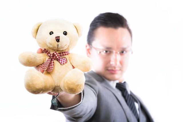 熊のぬいぐるみを差し出す外資系ビジネスマンの写真