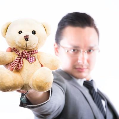 「熊のぬいぐるみを差し出す外資系ビジネスマン」の写真素材