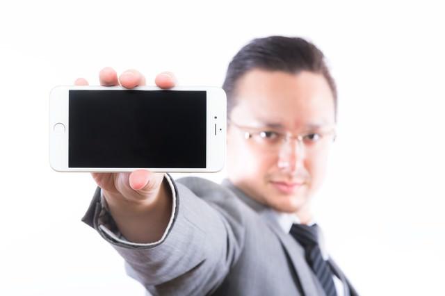 スマートフォンの画面(横)を見せるエンジニアの写真