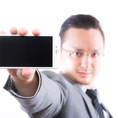 「スマートフォンの画面(横)を見せるエンジニア」の写真素材
