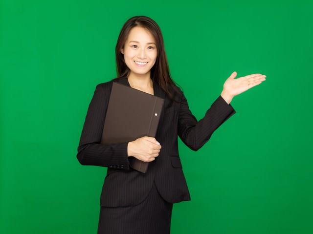 資料をもって案内するスーツ姿の女性(グリーンバック)の写真
