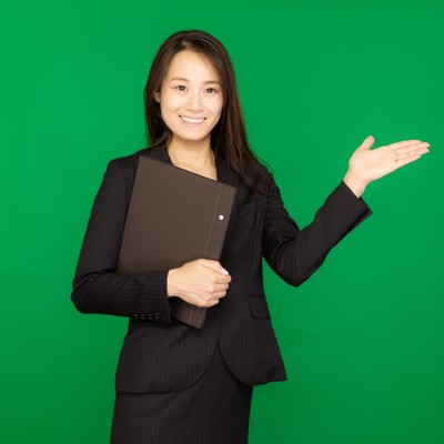 「資料をもって案内するスーツ姿の女性(グリーンバック)」の写真素材
