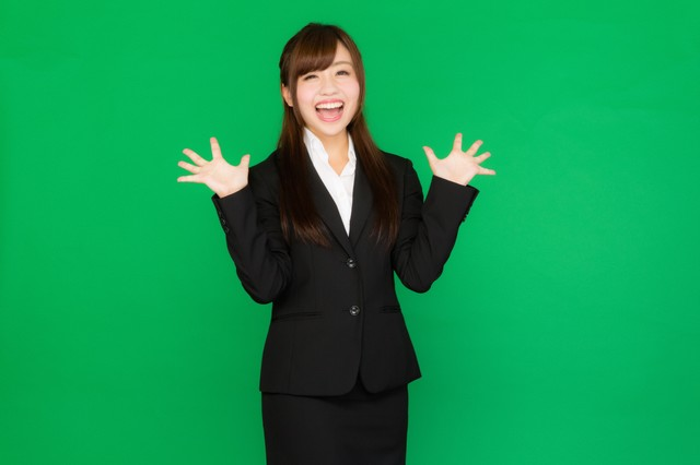 両手を広げて喜ぶスーツ姿の女性(グリーンバック)の写真