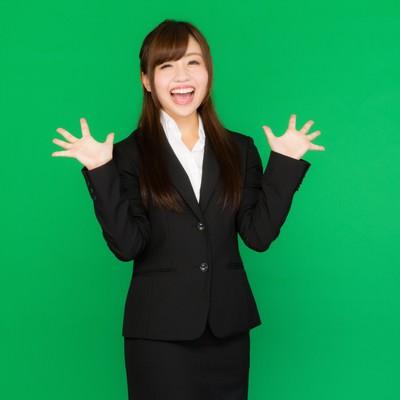 「両手を広げて喜ぶスーツ姿の女性(グリーンバック)」の写真素材