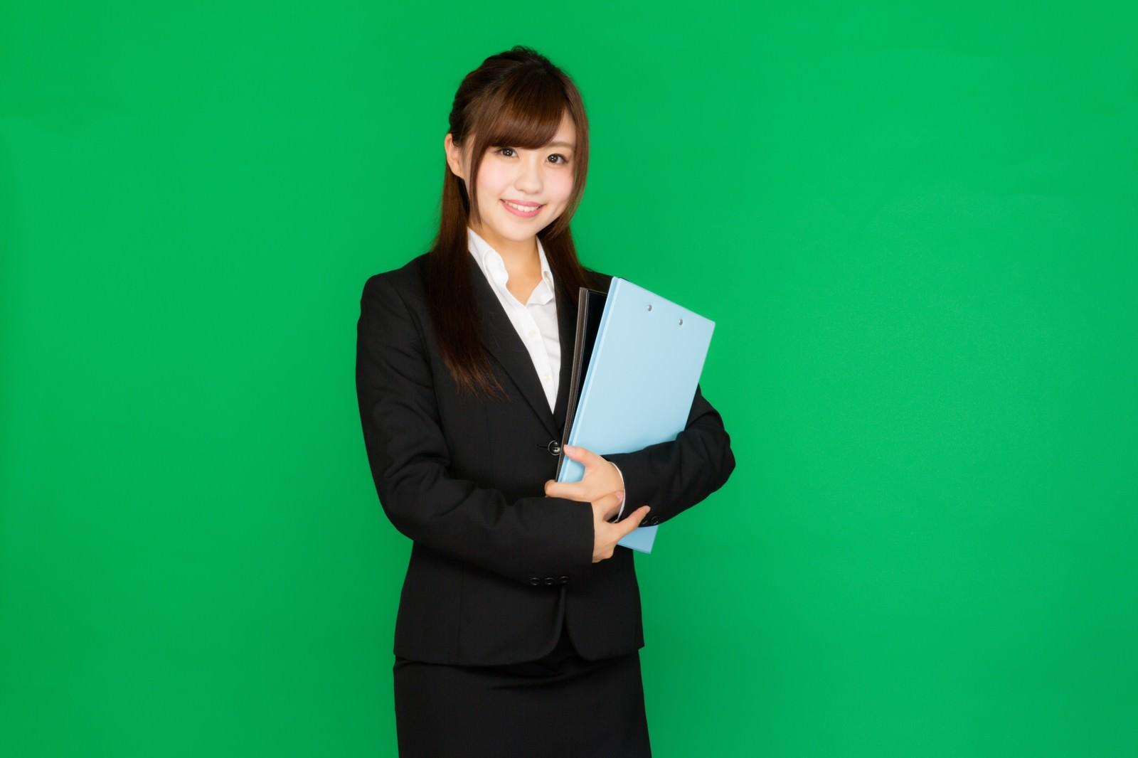 「会議に必要な書類を持ったスーツ姿の女性(グリーンバック)」の写真[モデル:河村友歌]