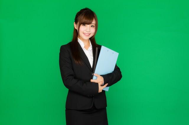 会議に必要な書類を持ったスーツ姿の女性(グリーンバック)の写真