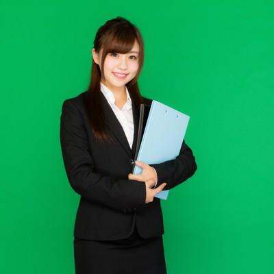 「会議に必要な書類を持ったスーツ姿の女性(グリーンバック)」の写真素材