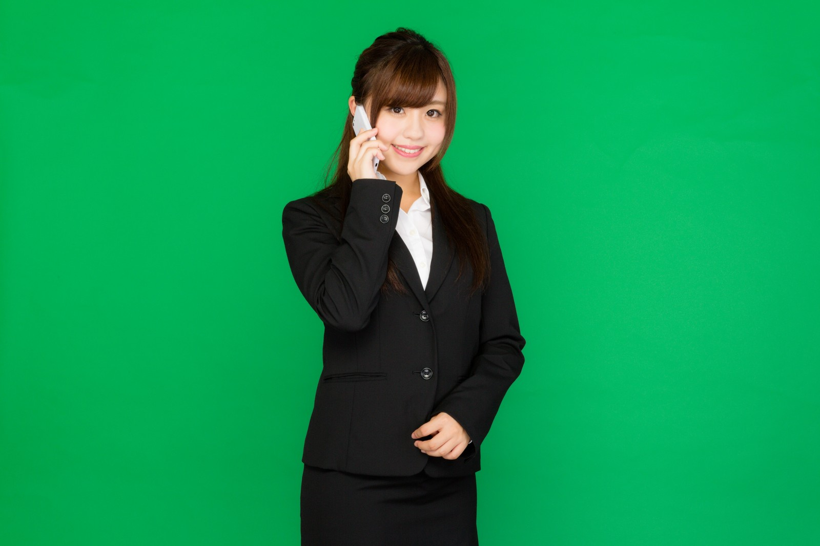 「電話に出る女性秘書(グリーンバック)」の写真[モデル:河村友歌]