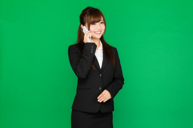 笑顔で電話対応する女性の写真