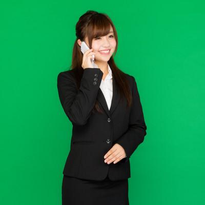「笑顔で電話対応する女性」の写真素材