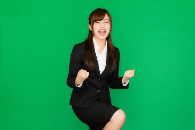 社内プレゼンが通って超喜ぶスーツ姿の女性(グリーンバック)の写真
