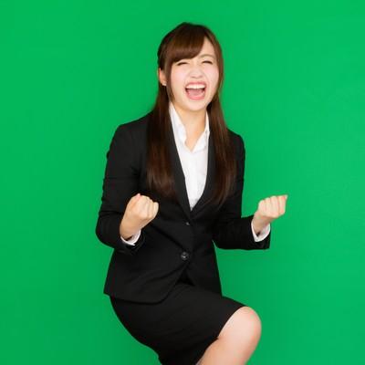「社内プレゼンが通って超喜ぶスーツ姿の女性(グリーンバック)」の写真素材