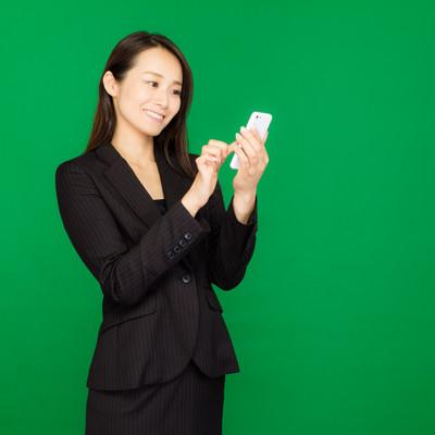 「スマートフォンで今夜の飲み会を予約(グリーンバック)」の写真素材
