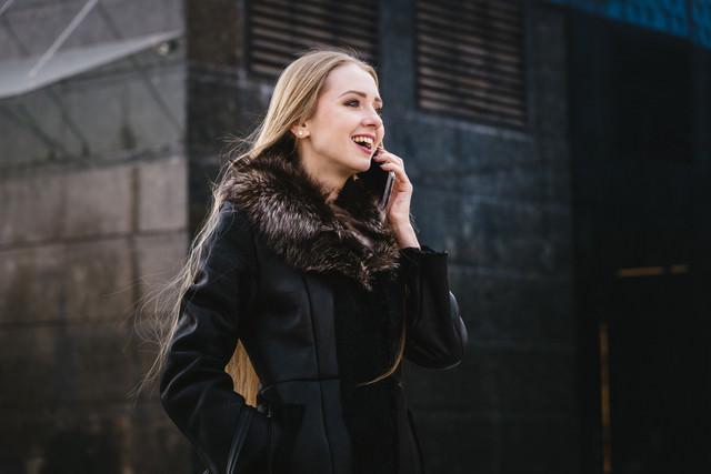 電話しながら笑顔になる外国人女性の写真