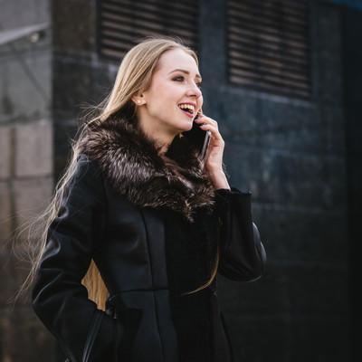 「電話しながら笑顔になる外国人女性」の写真素材