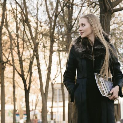 「公園で雑誌を持ったブロンド美女」の写真素材