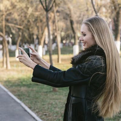 「公園をスマホで撮影するモデル」の写真素材