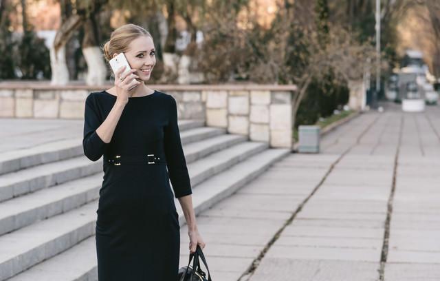 電話越しで微笑むブロンドモデルの写真