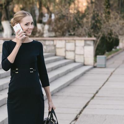 「電話越しで微笑むブロンドモデル」の写真素材